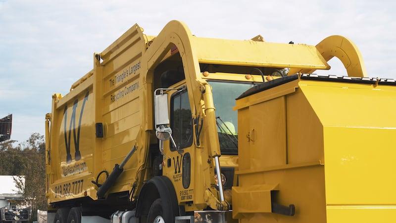 A yellow dump truck preparing to lift dumpster.
