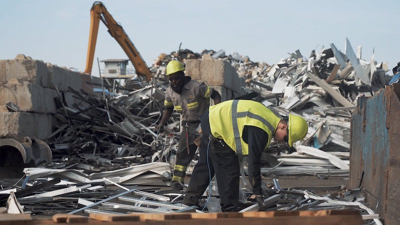 Two Wall Recycling employees working in a scrap yard.