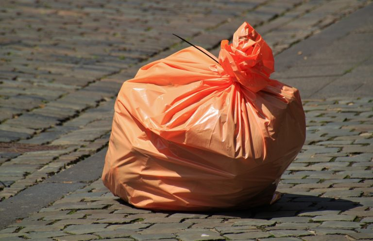 orange trash bag to be thrown into a rented dumpster